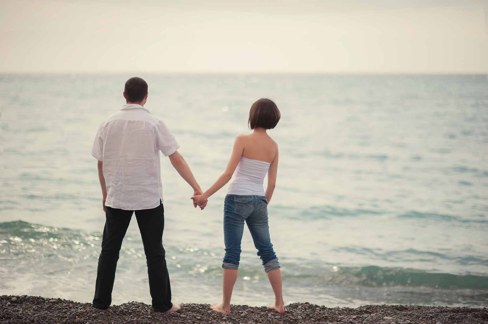 Beautiful young couple standing on the beach and holding hands