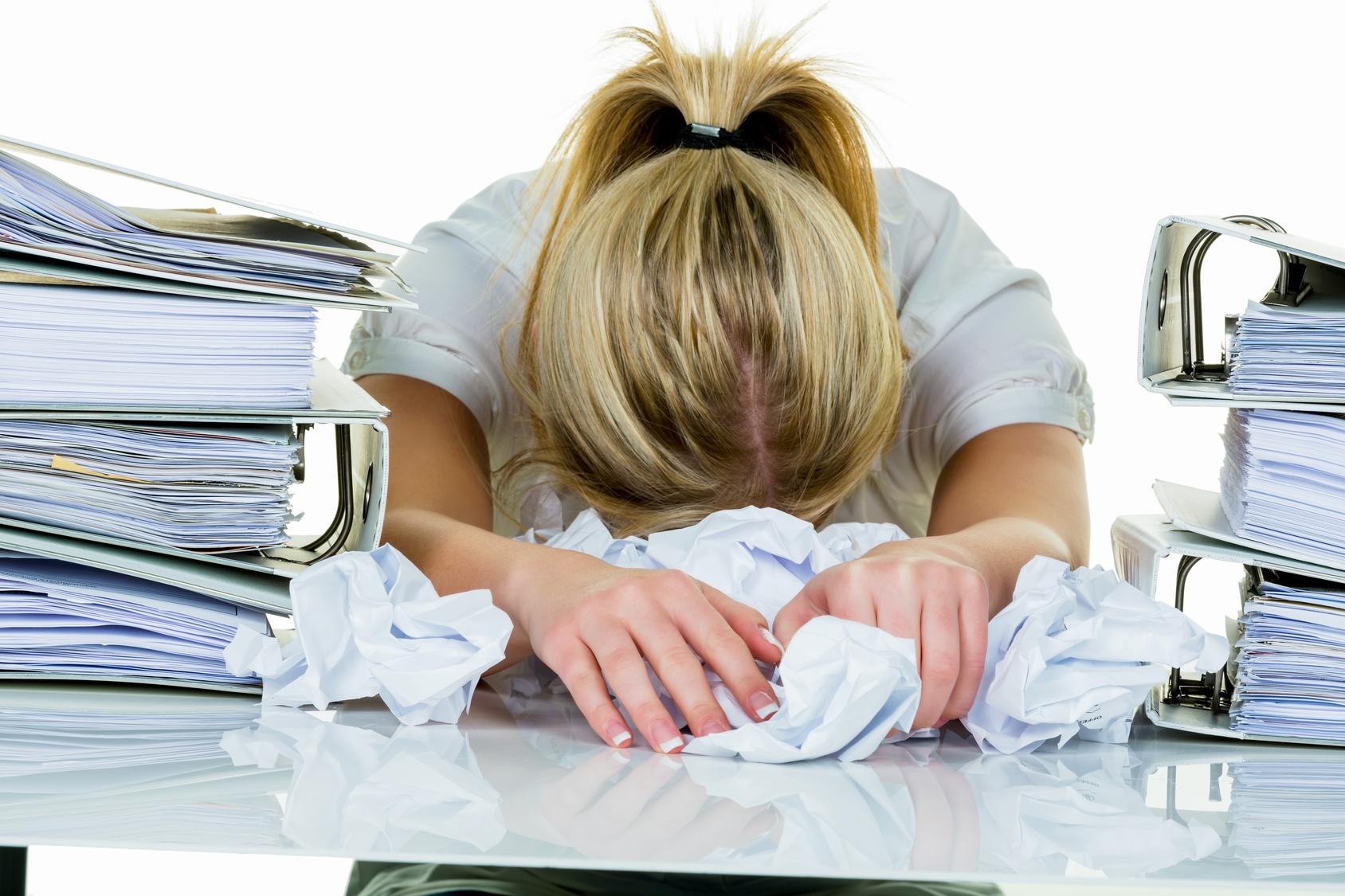 Eine junge Frau verzweifelt im Büro zwischen vielen Aktenordnern und zerknülltem Papier.Symbolfoto für Stress, Burnout und Überarbeitung.