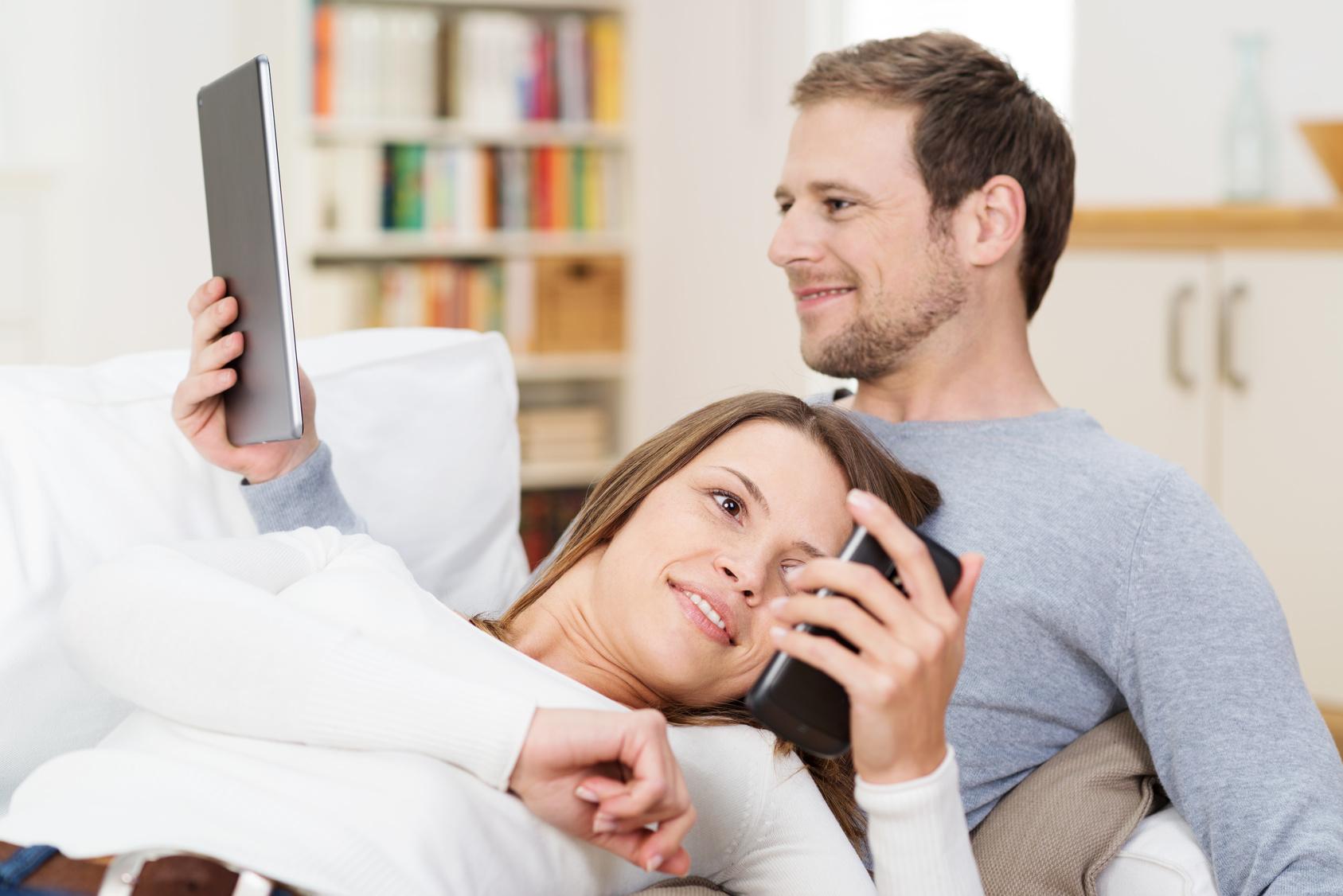 junges paar zuhause liest mit smartphone und tablet-pc