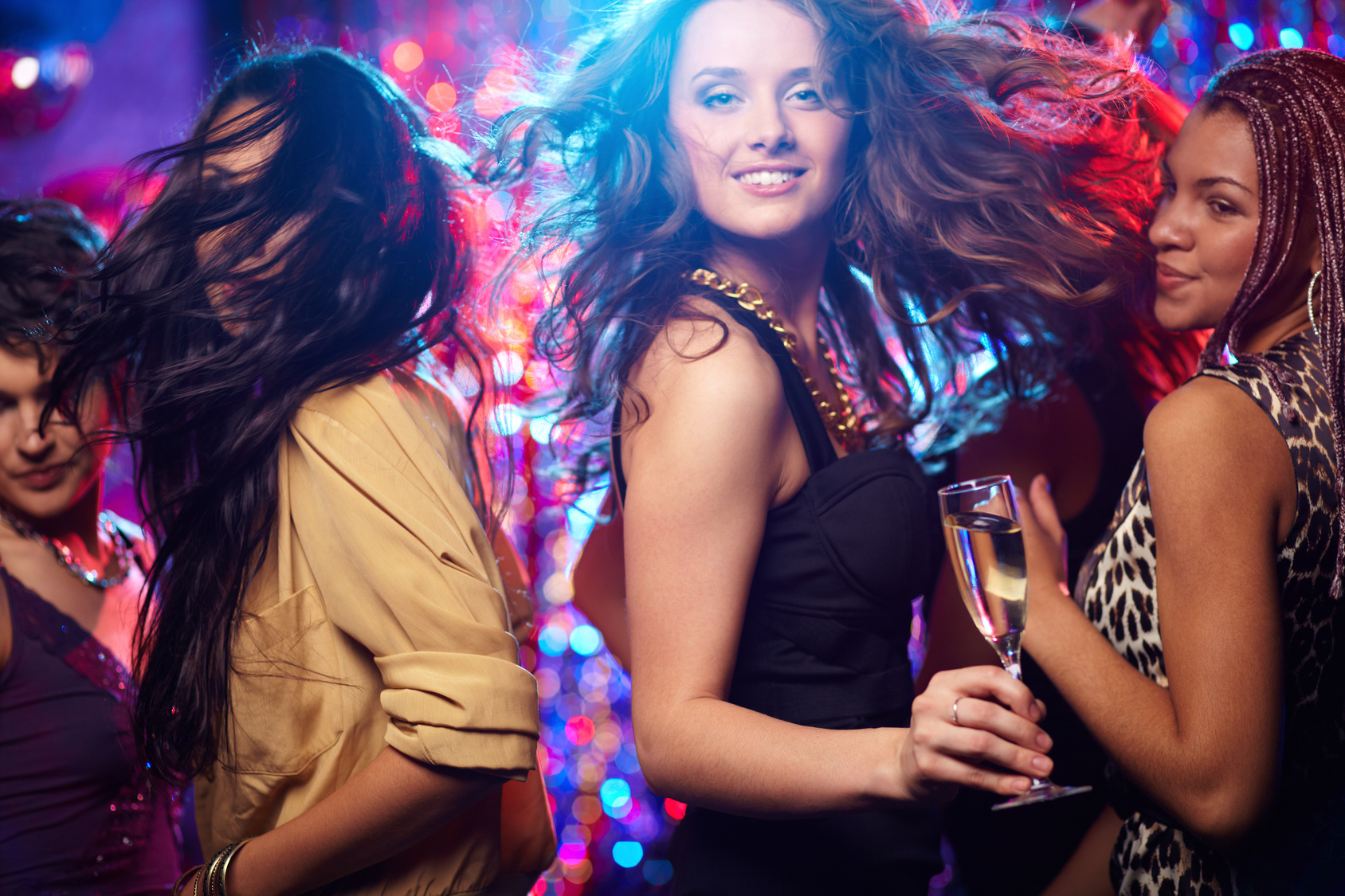 Young woman looking at camera while dancing at nightclub among her friends