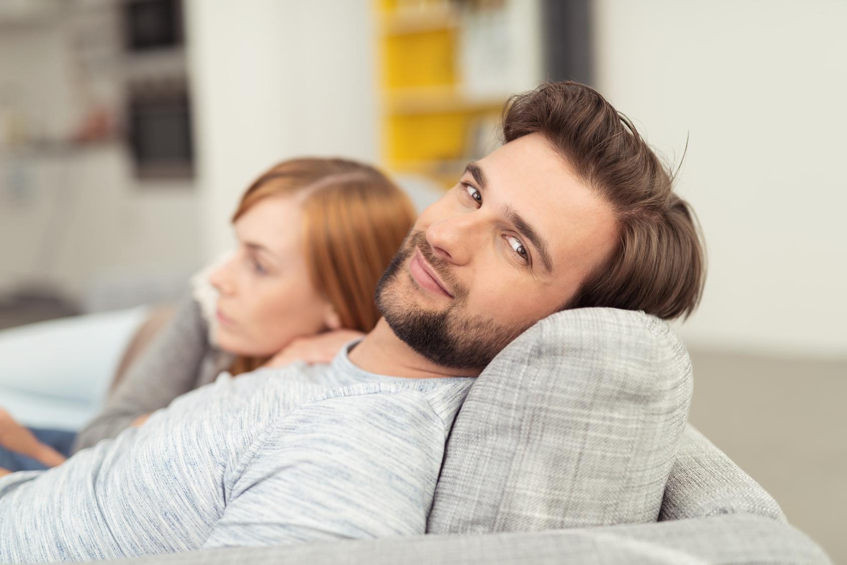 mann liegt entspannt auf dem sofa mit seiner freundin