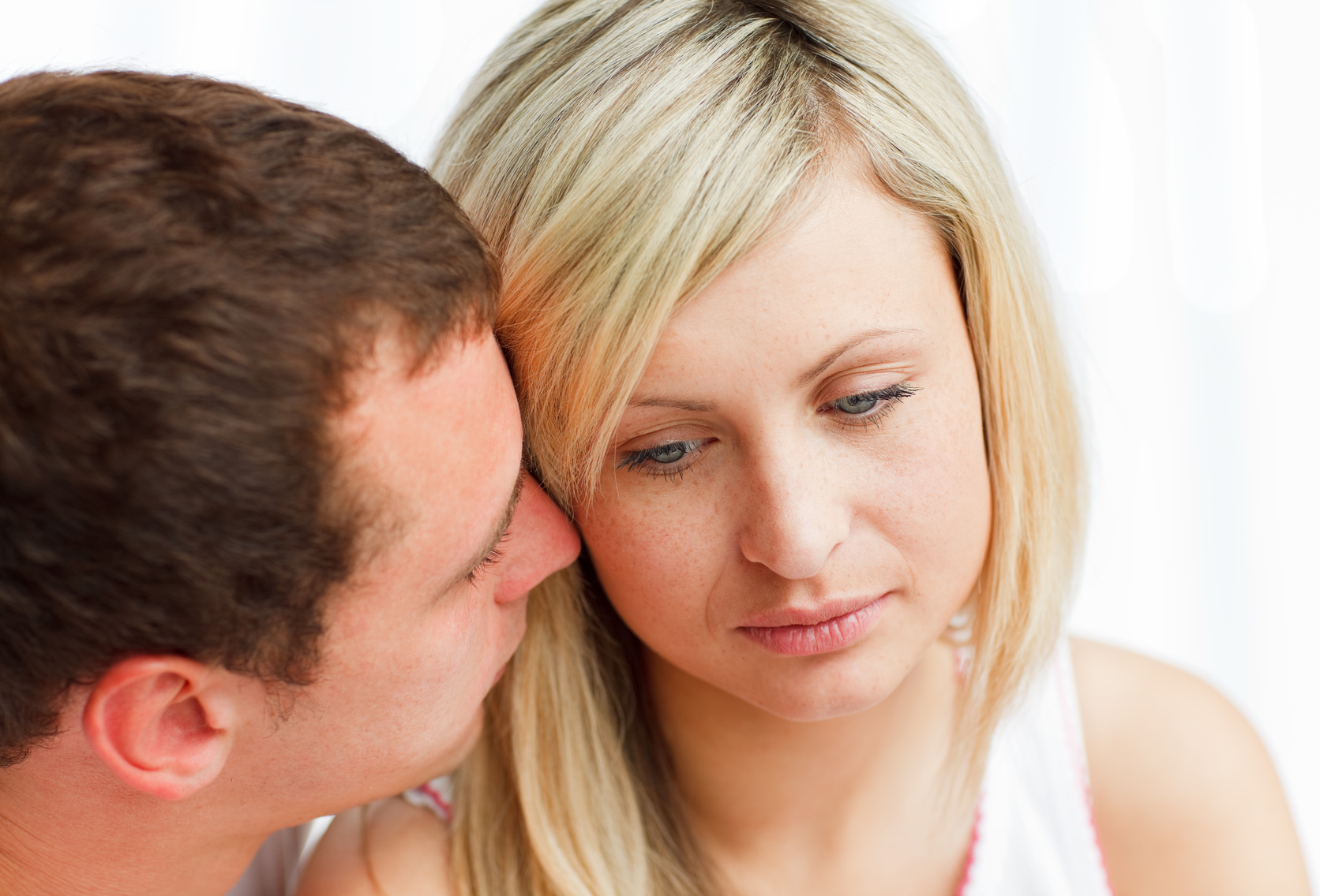 Close-up of a man kissing a sad woman