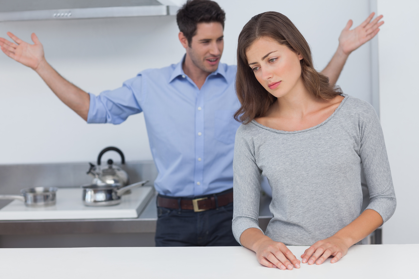 Man gesturing to wife during a dispute in the kitchen