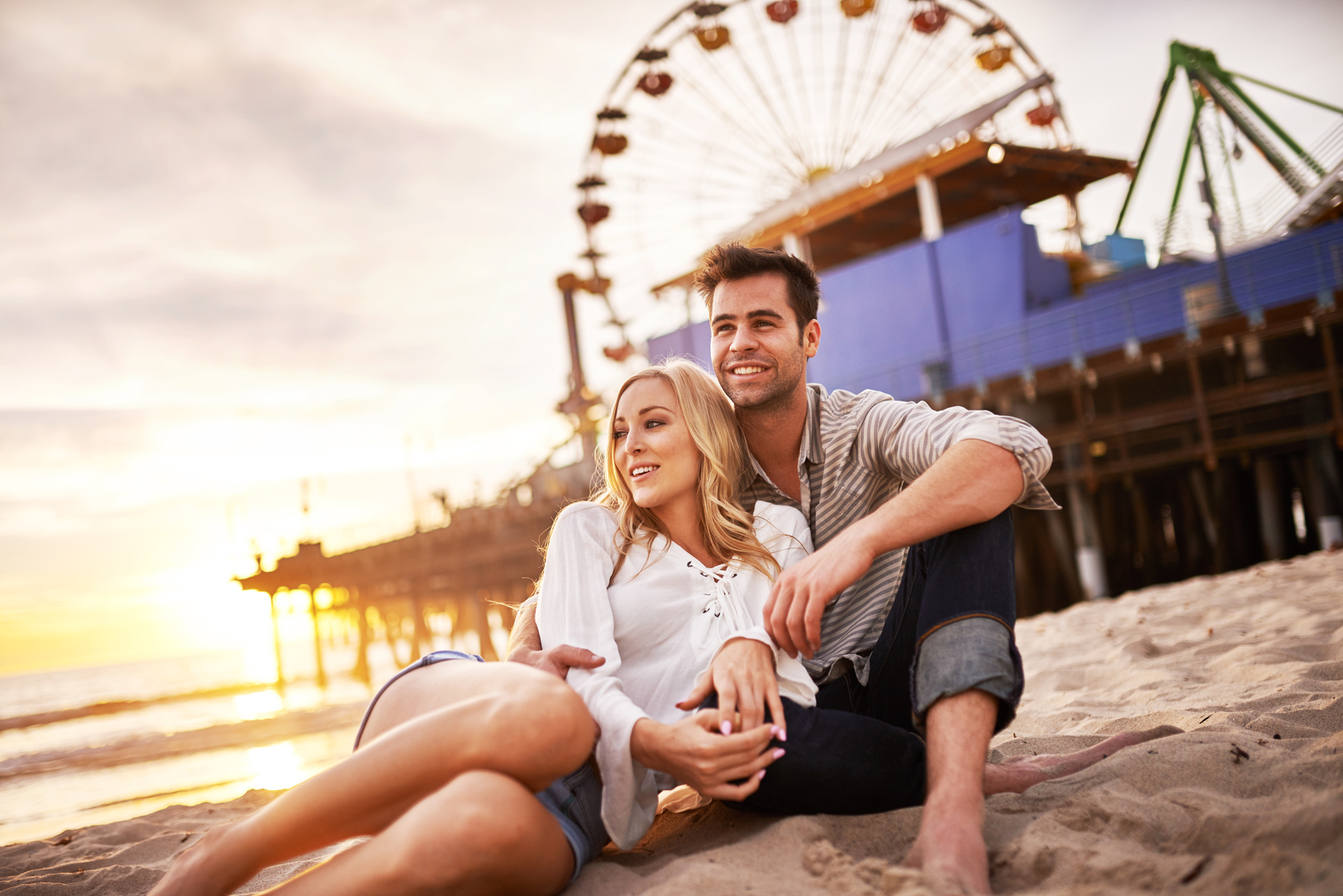 happy romantic couple at santa monica during sunset