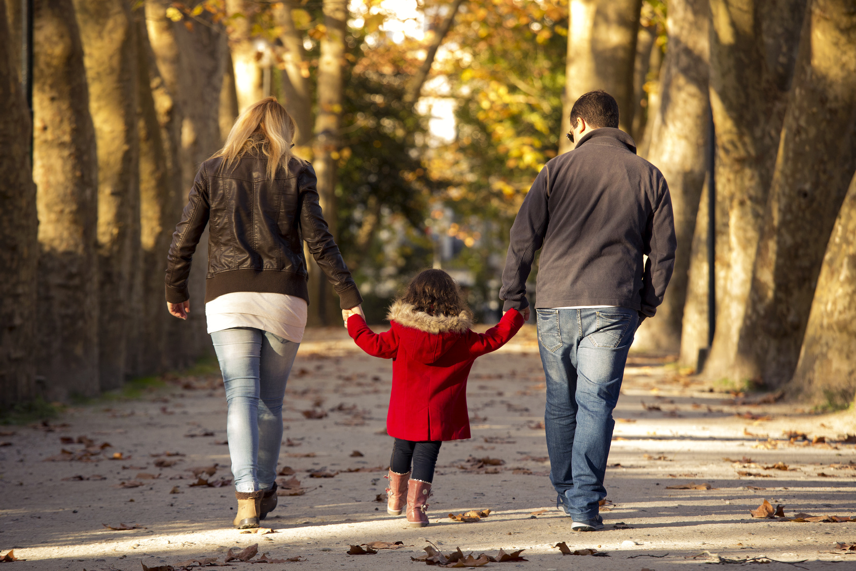 Outdoor portrait of a happy family walking together and enjoying the fall season