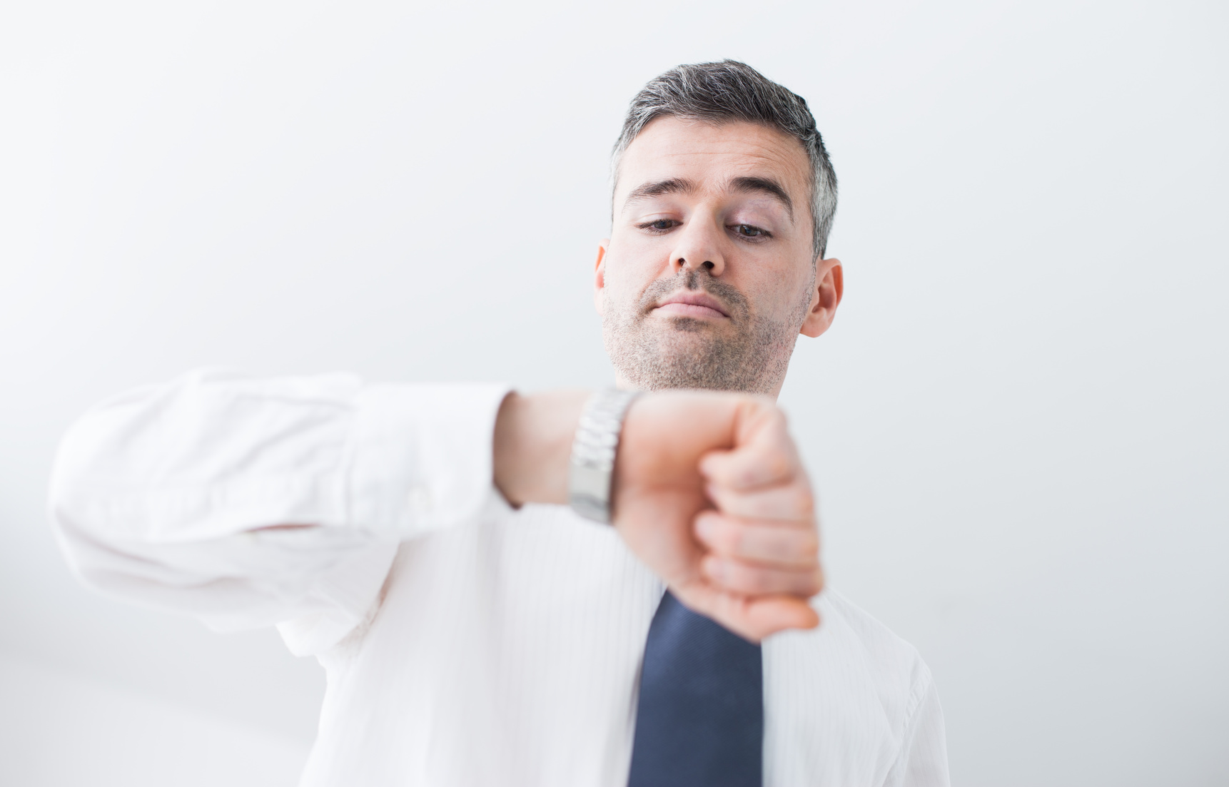 Confident businessman checking the time on his watch, efficiency and planning concept