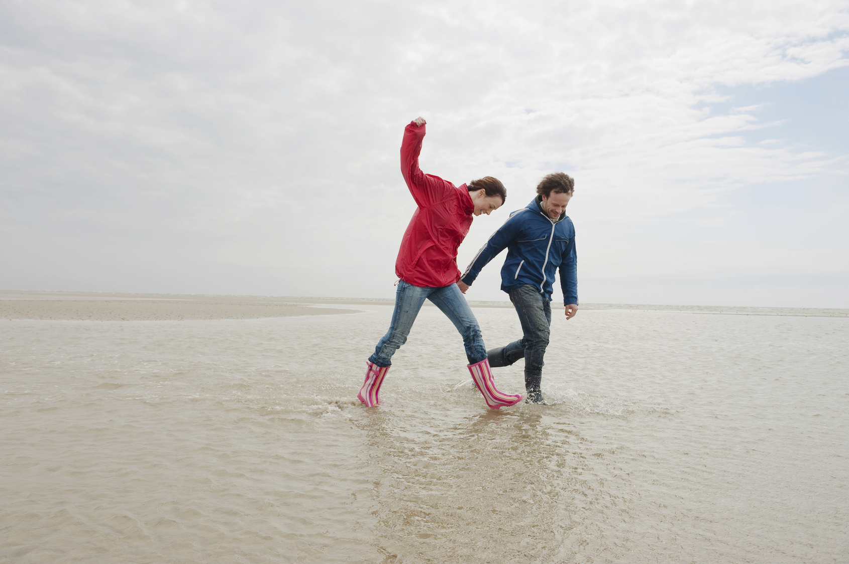Germany, St. Peter-Ording, North Sea, Couple holding hands and walking on beach