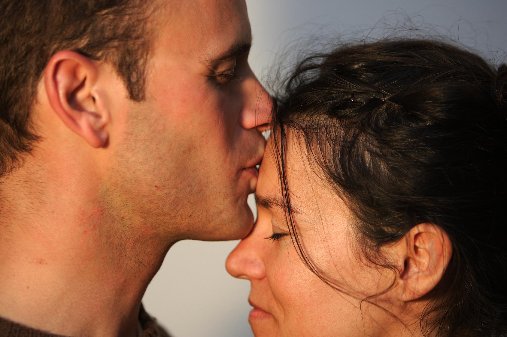 Couple qui s'échange des tendresses dans une lumière de coucher de soleil. Image d'amour et de tendresse entre un jeune homme et sa fiancée.