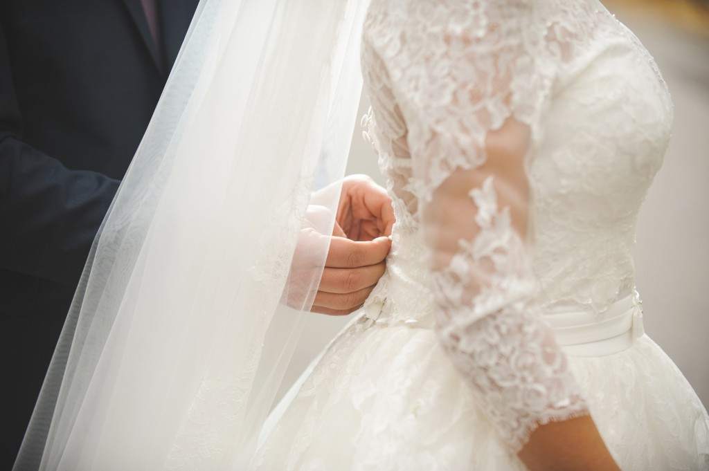 groom helping bride to button corset of wedding dress