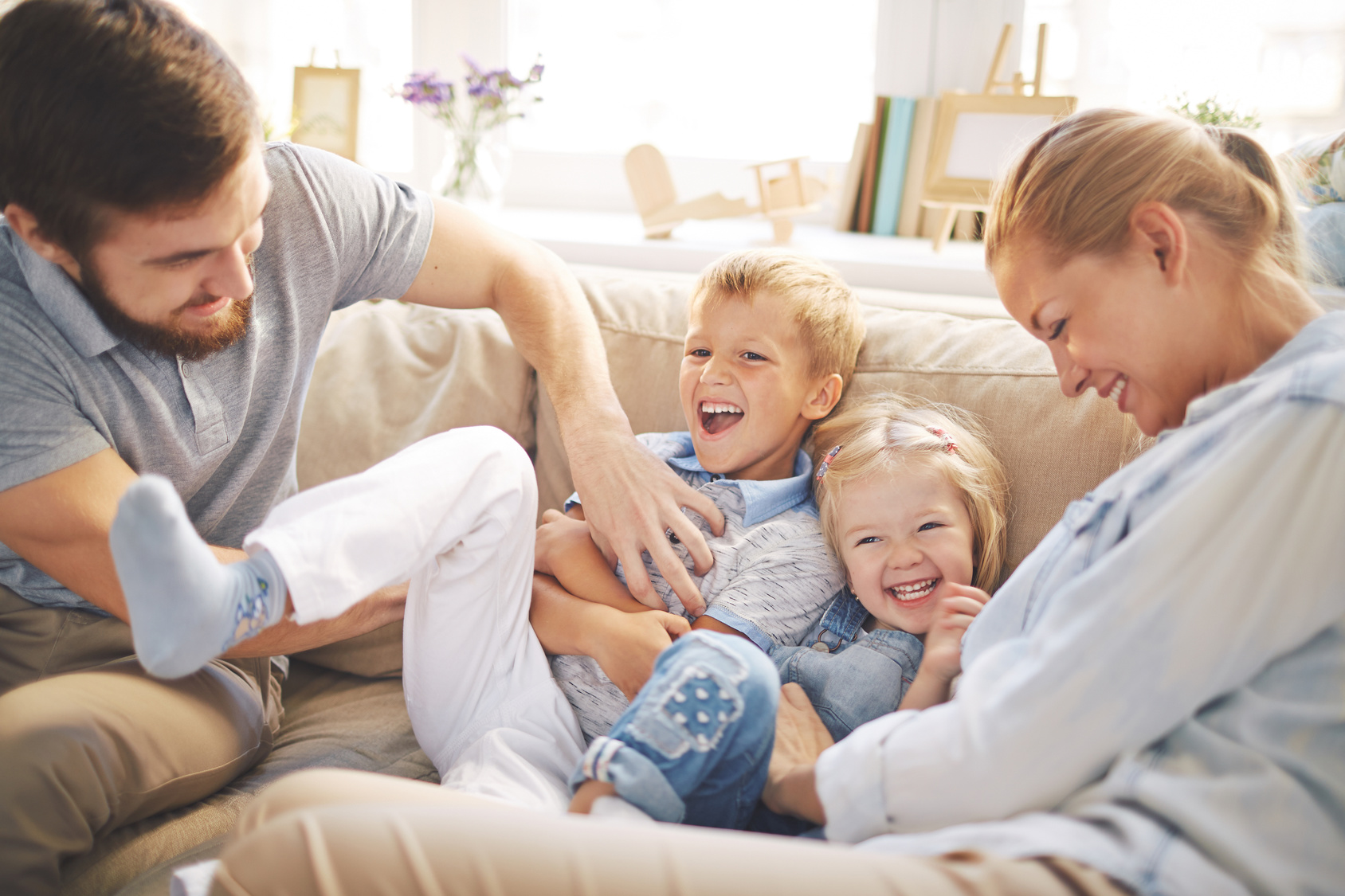 Happy young parents playing with cute children on sofa
