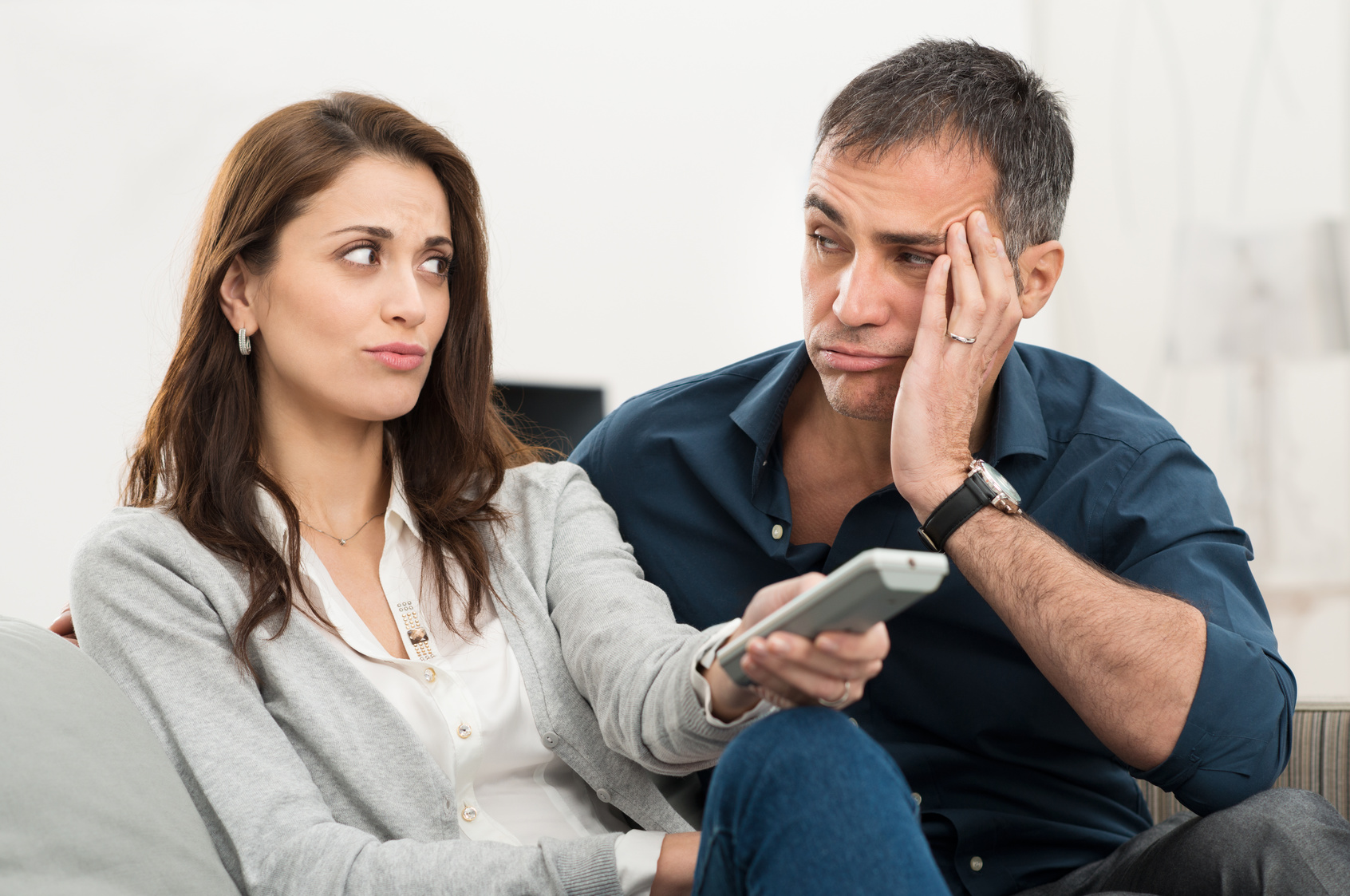 Frustrated Couple Looking At Each Other While Watching Television Sitting On Couch