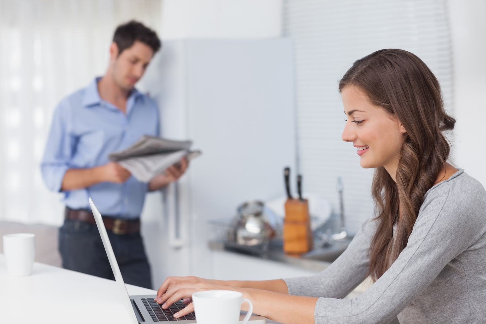 Attractive woman using her laptop in the kitchen with her husband reading a newspaper on the background