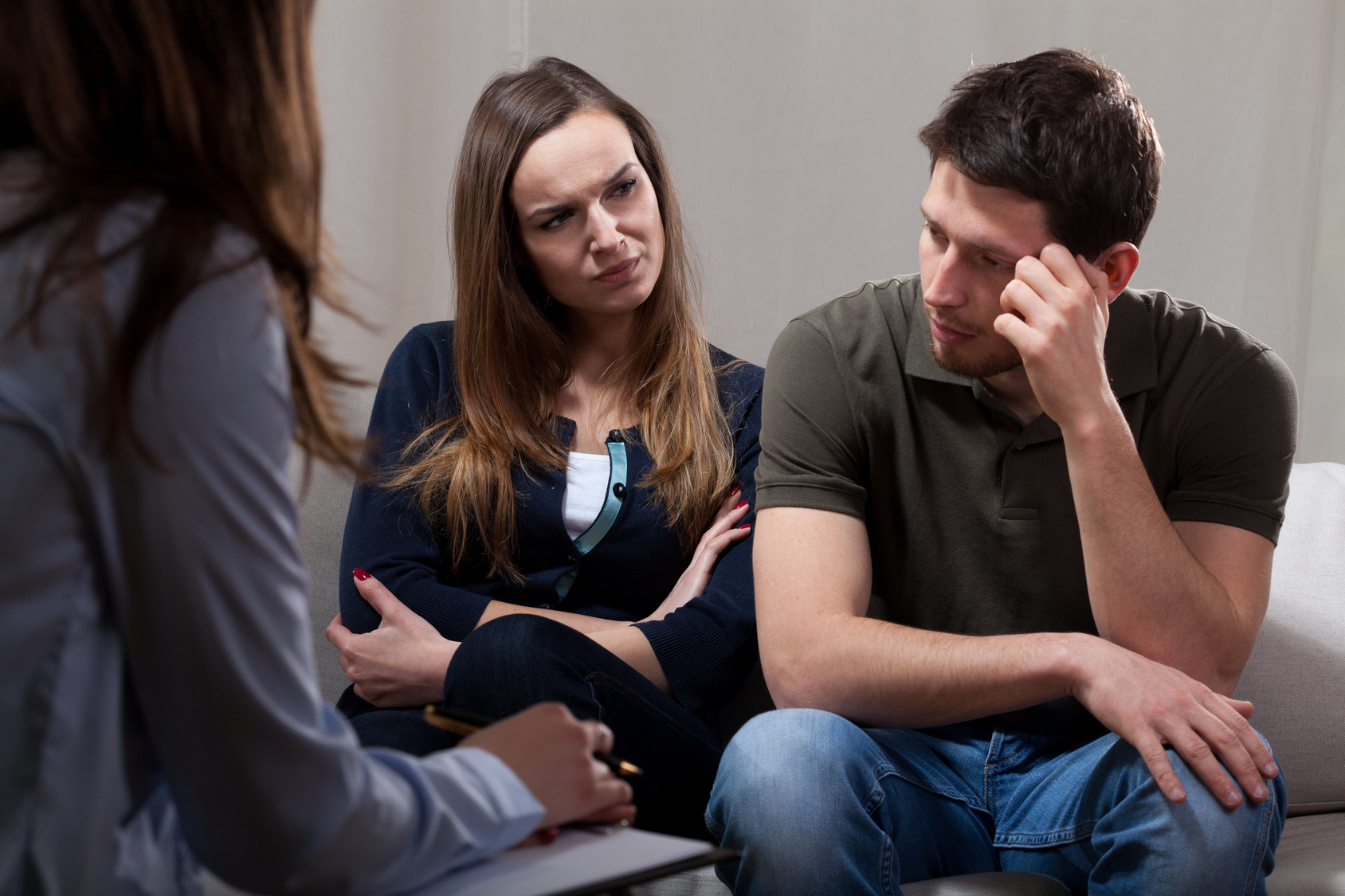 Unhappy at odds couple sitting on psychotherapy session