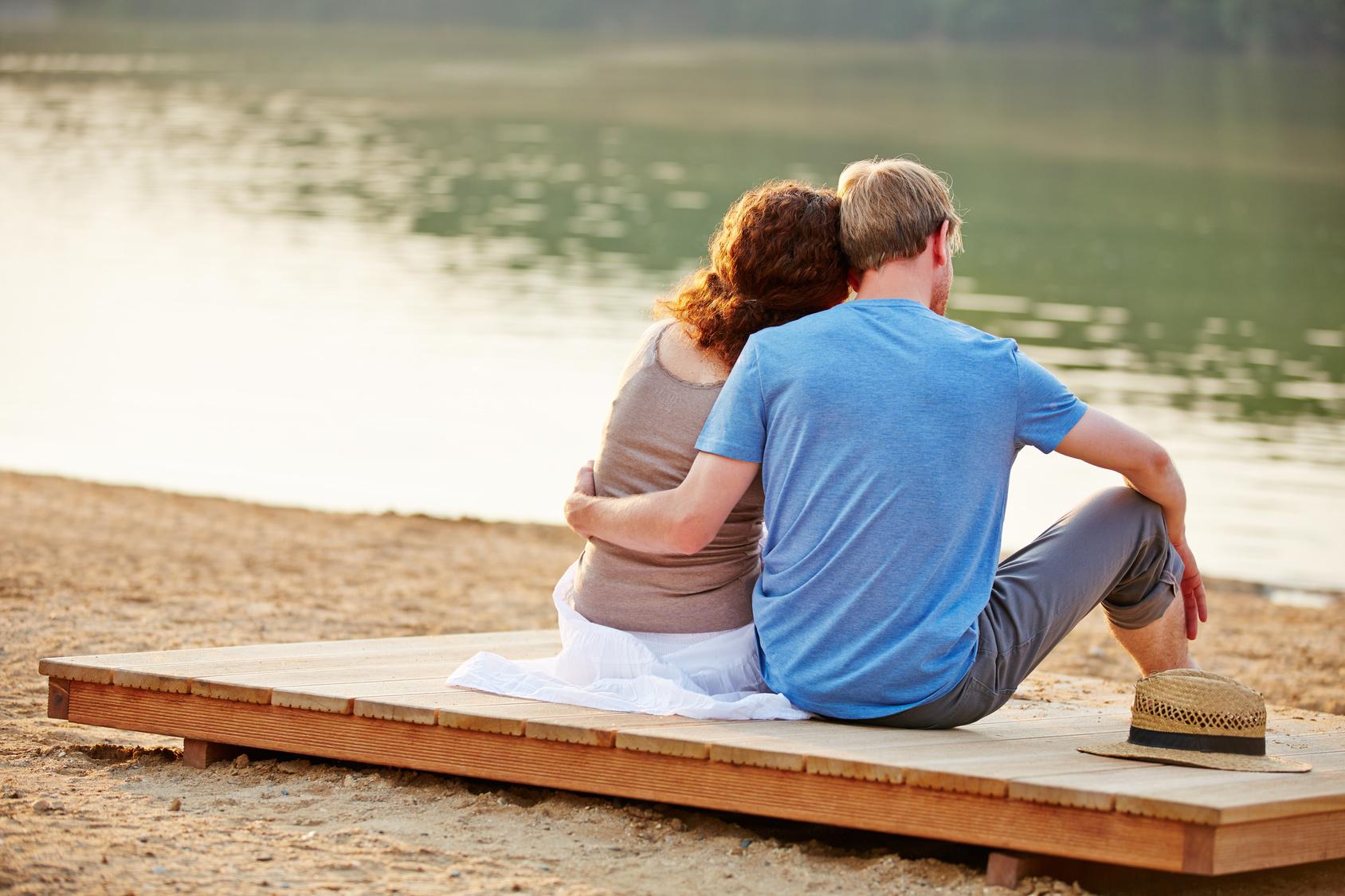 Entspanntes Paar im Sommer sitzt verliebt am Strand