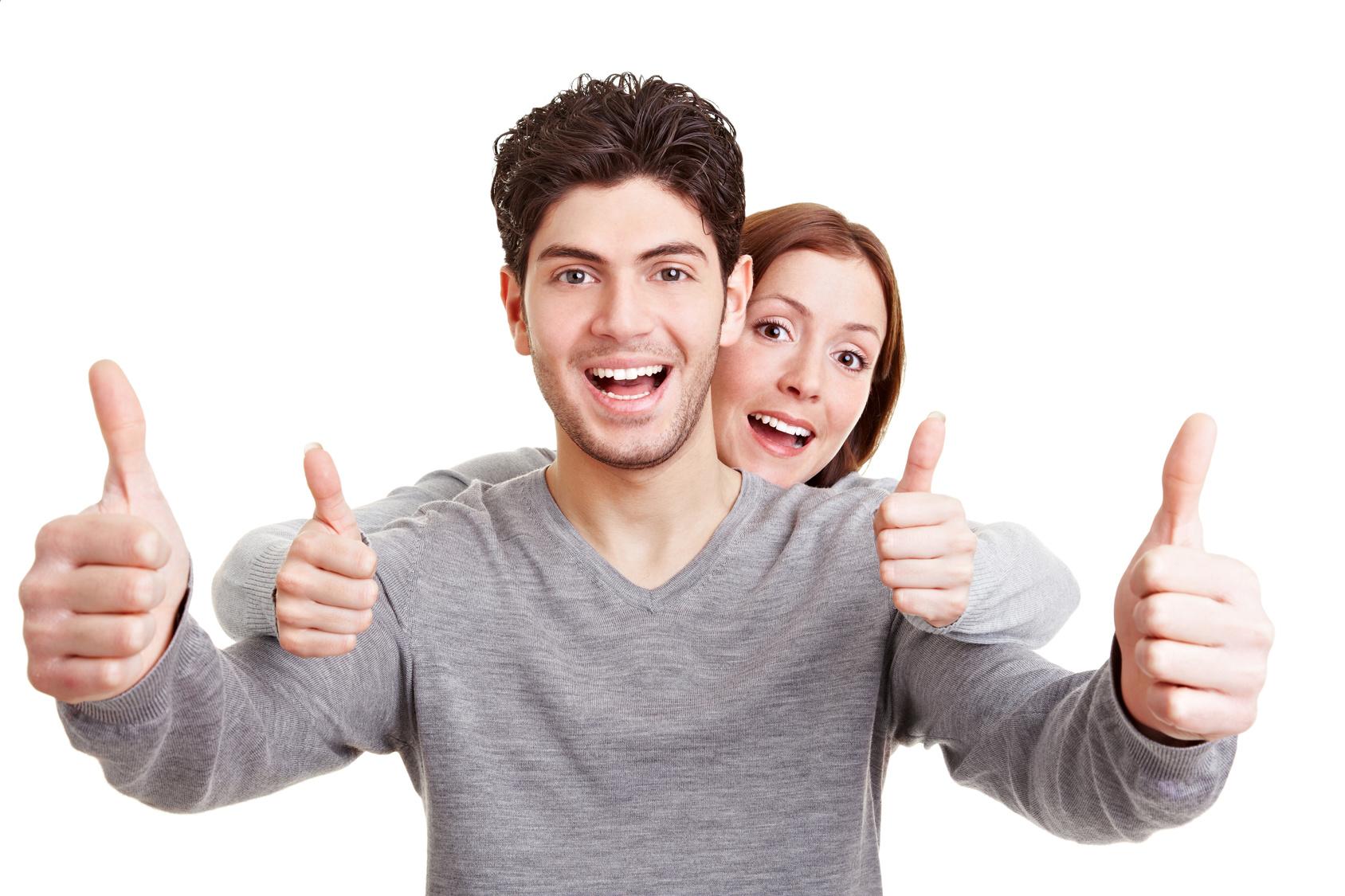 Lachendes Paar hält beide Daumen hoch