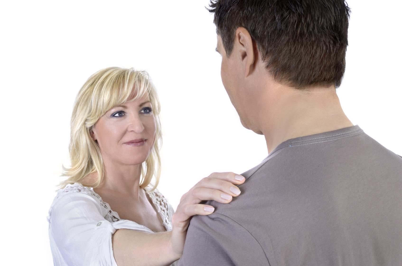Reife Frau legt Hand auf die Schulter ihres Ehemanns, Studio Shot
