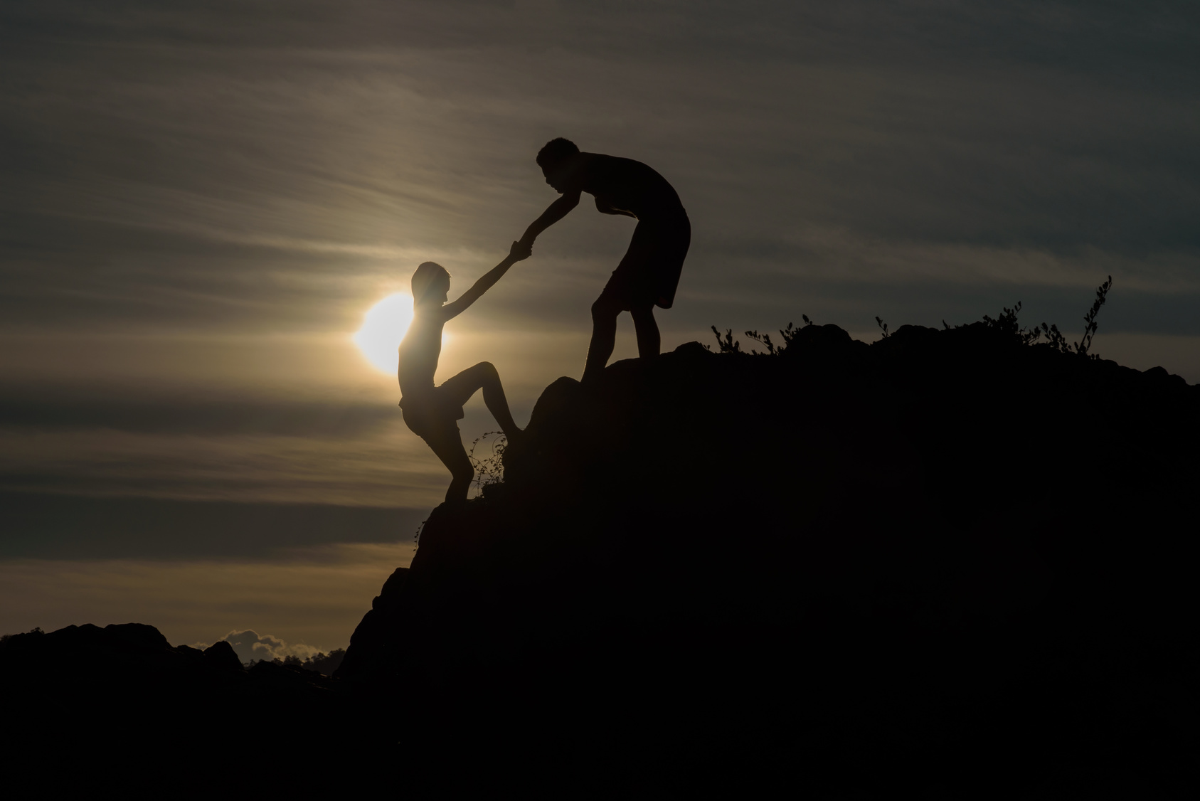 Silhouette of two boys helped pull together climbing