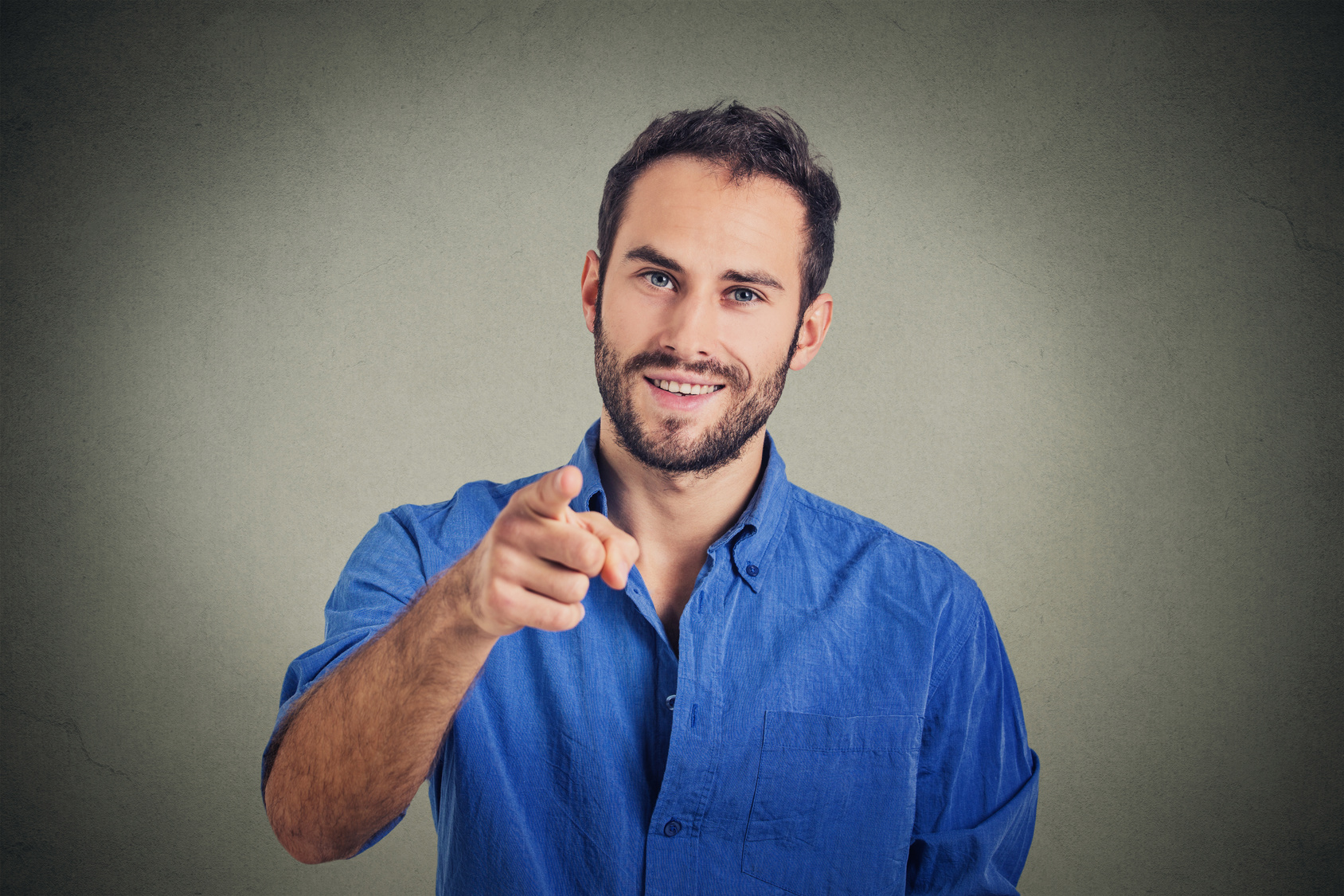 Handsome young man pointing finger at you isolated on gray wall background